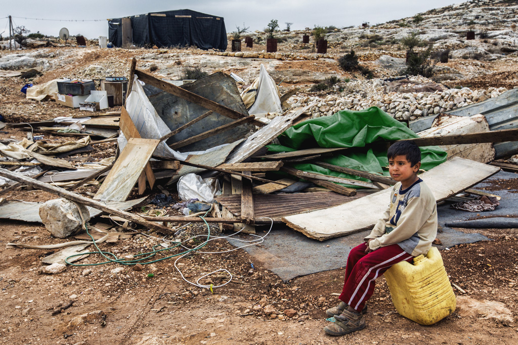 A boy sits a top a water can in front of the ruins of his family home, which was destroyed the day before. Dec. 28, 2013. West Bank, Palestinian Territories. (Photo by Gabriel Romero/Alexia Foundation ©2014)