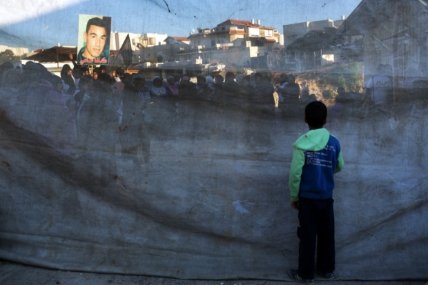 A boy watches through a cloth as protesters march in the Bedouin town of Rahat after the killing of two locals by Israeli forces (AFP)