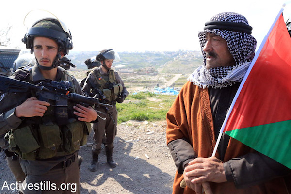 Palestinian, Israeli and international activists protest against Israeli plans to build new settlements in the E1 area of the West Bank, Eizariya, West Bank, March 17, 2015. (Ahmad al-Bazz/Activestills.org)