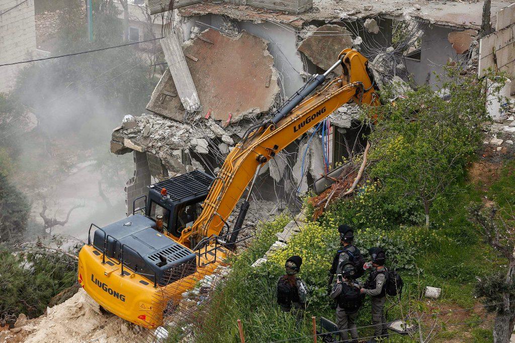 Israeli Border Police officers stand guard while anIsraeli bulldozer demolish a Palestinian building, Bethlehem, April 2, 2019. (Wisam Hashlamoun/Flash90)