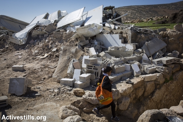 A Palestinian girl walks back from school to her demolished home after it was torn down by Israeli bulldozers in the village of Khirbet al-Halawah in firing zone 918, which includes several villages, south of Hebron, West Bank, February 3, 2016. (Activestills.org)