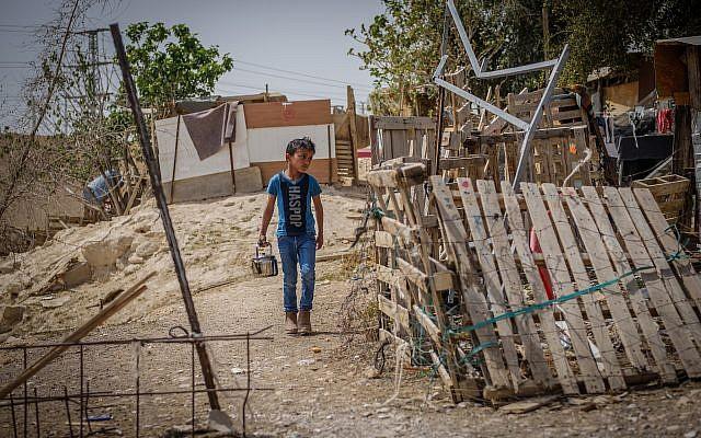 A boy walks through the Bedouin village of Khan al-Ahmar, near the Jerusalem-Dead Sea highway, on April 13, 2018. (Yaniv Nadav/ Flash90)