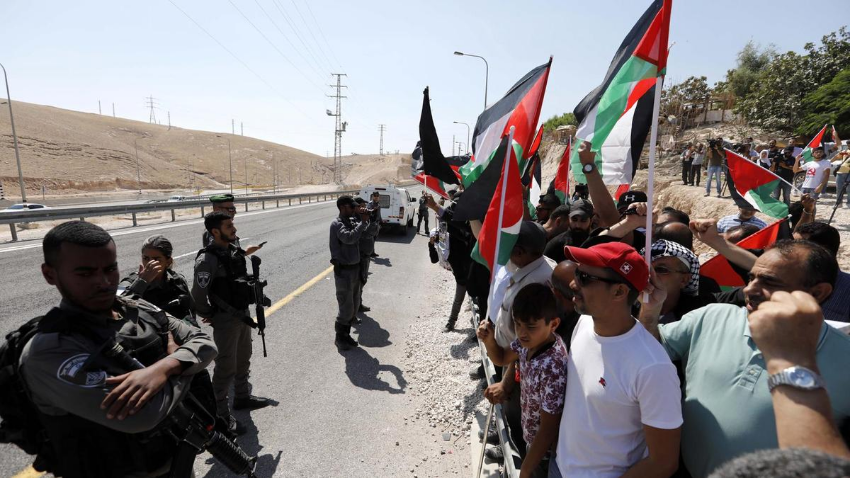 Demonstrators wave Palestinian flags in front of Israeli troops as they protest against Israel's plan to demolish the Palestinian Bedouin village of Khan Al Ahmar. EPA