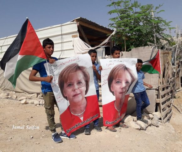 "Children in Khan al-Ahmar hold posters of German Chancellor Angela Merkel saying ""Save Khan al Ahmar"" on Tuesday, Oct. 2 (Photo Courtesy of Jamal Saifan)"
