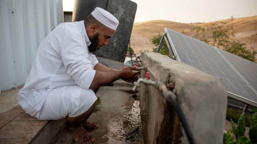 An imam in the Bedouin village of Khan al-Ahmar prepares for prayers, May 3, 2020.Credit: Emil Salman