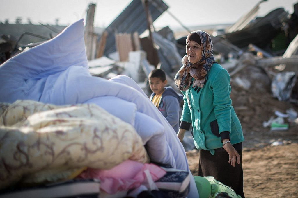 Bedouin collect their belongings from the ruins of their demolished homes in the unrecognized village of Umm al-Hiran in the Negev desert, in the in the Southern Israel, January 18, 2017. (Hadas Parush/Flash90)