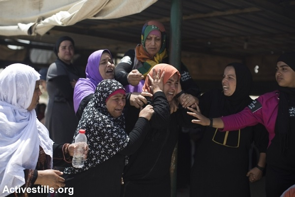 Bedouin women cry as they watch their house being destroyed during the demolition of the unrecognized Bedouin village of Al Arakib in the Negev desert. Israeli authorities have demolished the village over 70 times since 2010, June 12, 2014. (Oren Ziv/Activestills)