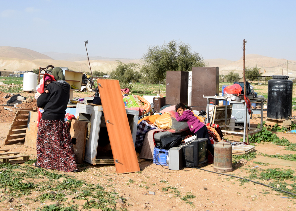 Family members next to the contents 0of their demolished home in Fasayil al-Wasta. Photo by 'Aref Dagharmeh, B'Tselem, 16 Jan. 2