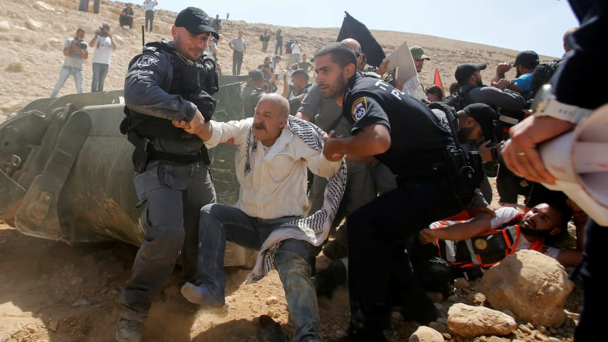 Israeli forces detain a Palestinian man as they protest against Israel's plan to demolish the Palestinian Bedouin village of Khan al-Ahmar, in the West Bank September 14, 2018. Credit: Mussa Qawasma/Reuters
