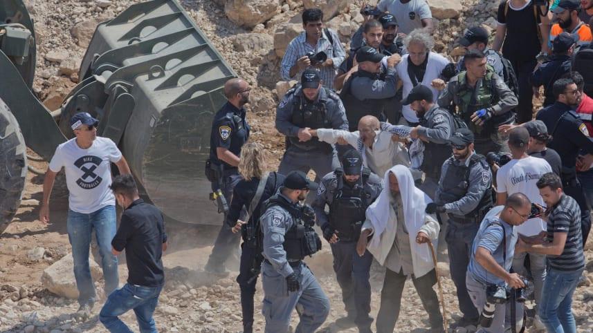 Israel Border Police confront protesters and activists blocking an IDF bulldozer operating in Khan al-Ahmar, June 9, 2019.Credit: Nasser Nasser / AP